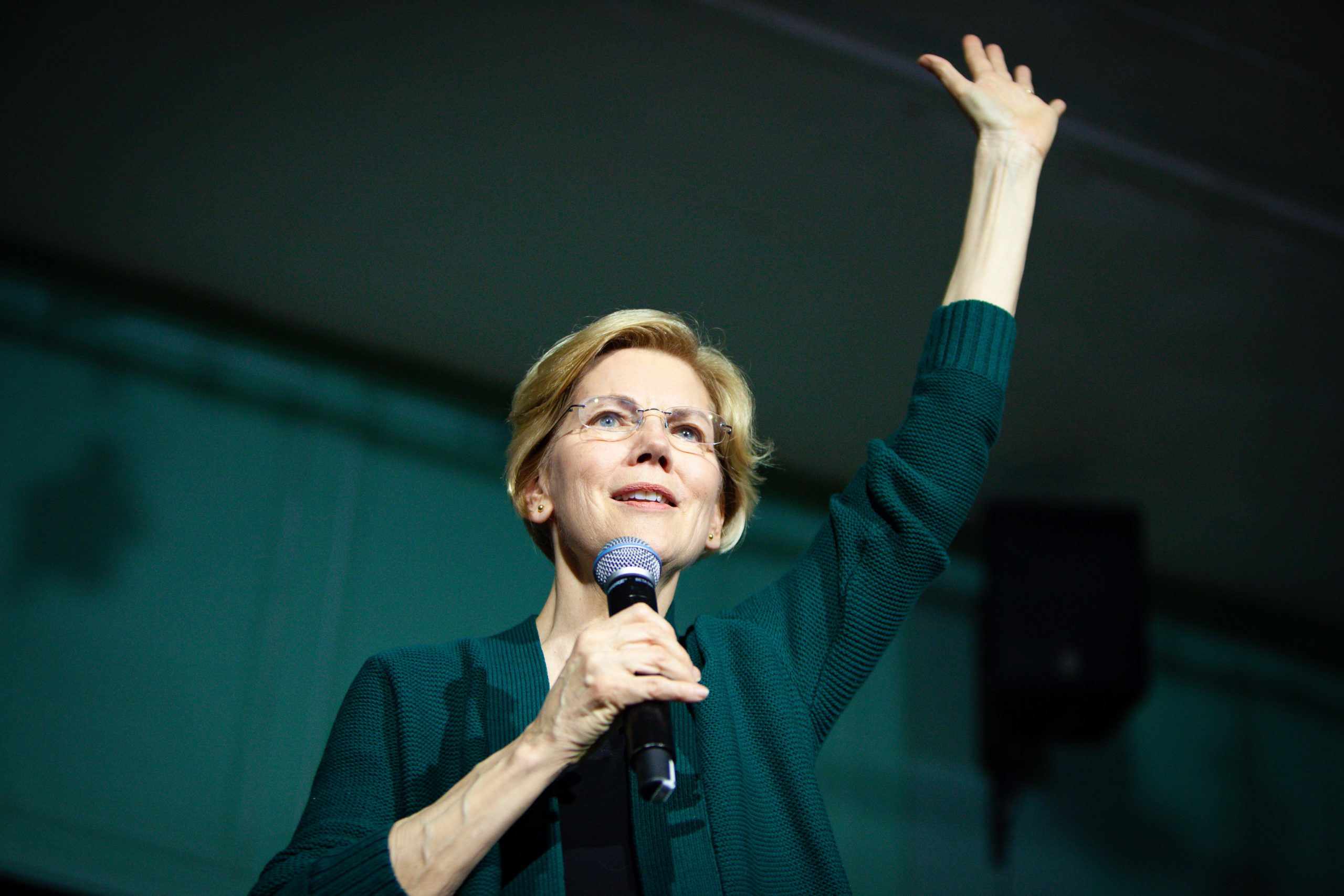 Elizabeth Warren with microphone in hand and other hand raised